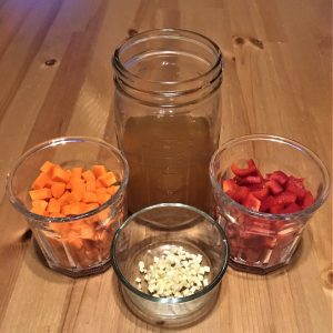 Glass containers filled with prepped broth, carrots, peppers, and garlic on a wooden table top