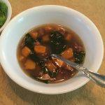 bowl of apple sausage sweet potato soup next to a salad