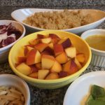 Create your own grain bowl ingredients: serving dishes with quinoa, radicchio, peaches, dressing, slivered almonds, and avocados