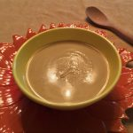 Bowl of curried cauliflower soup on a flower-shaped charger with a wooden spoon