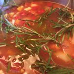 Pot of vegetable and bean soup with rosemary sprigs