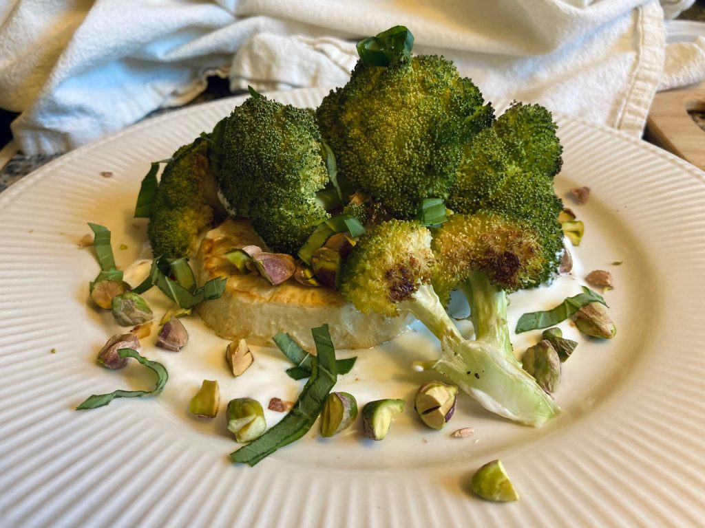 Roasted broccoli and celery root over yogurt with pistachios and basil