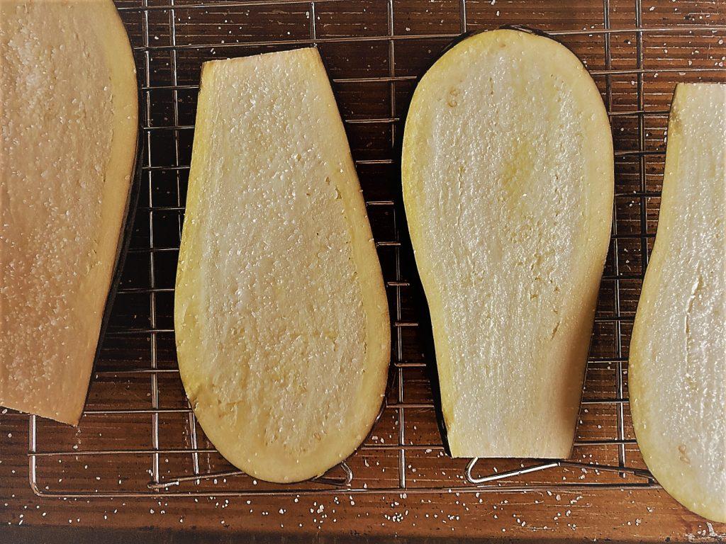 Salted eggplant slices on rack