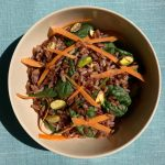 Bowl of red and brown rice with baby spinach, shredded carrots and pistachios