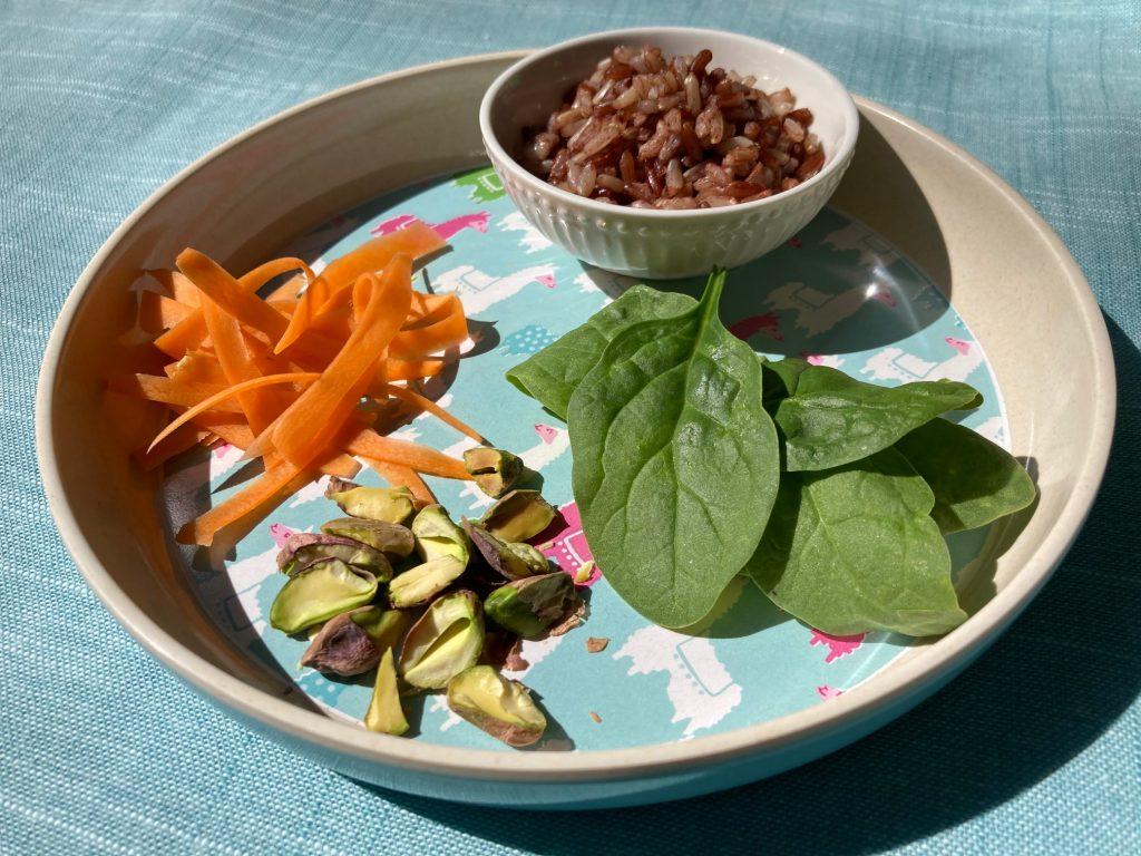 Child's plate with shredded carrots, pistachios, baby spinach and a bowl of rice